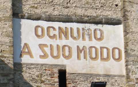 Il motto Ognuno a suo modo riportato sul campanile della chiesa di Coazze